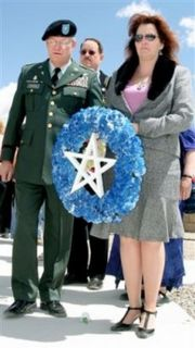 Roberta Stewart holding a wreath for her late husband: Sgt. Patrick Stewart